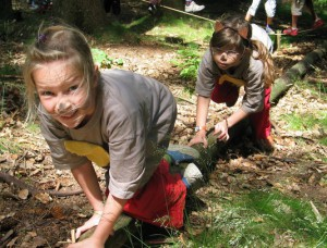 Das Bild zeigt zwei Mädchen, die als Tiere verkleidet sind. Sie krabbeln auf allen Vieren über einen dünnen Baumstamm.