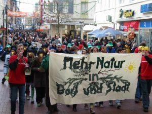 """Eine Demonstrationszug wird gezeigt. Die vorderen Menschen tragen ein Banner mit der Forderung """"Mehr Natur in Dorf und Stadt."""""""