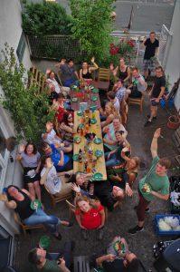Das Bild zeigt eine Gruppe junger Menschen, die sich im Innenhof unserer Geschäftsstelle um einen Tisch zum Essen versammelt haben. Das Foto wurde aus der Vogelperspektive aufgenommen und die Anwesenden winken Richtung Kamera.