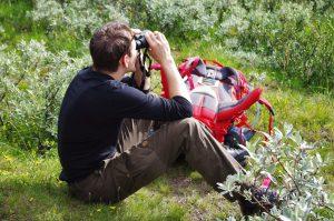 Das Bild zeigt einen jungen Mann der auf dem Waldoden sitzend in ein Fernglas sieht. Vor ihm liegt sein Wanderrucksack.