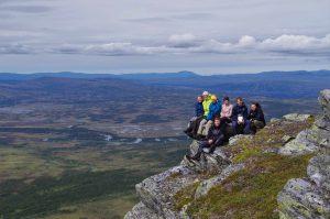 Auf einem Berghang sitzt eine Gruppe von Jugendlichen.