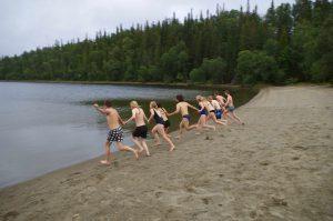 Eine Gruppe Jugendlicher in Badeklamotten hält sich an den Händen und läuft gemeinsam auf einen See zu.