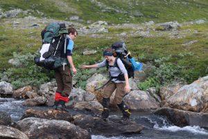 Zu sehen sind zwei Wanderer die gemeinsam einen Bach überqueren.