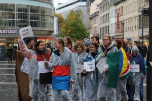 """Zu sehen sind eine Gruppe Jugendliche in der Wiebadener Innenstadt. Sie tragen weiße Maleranzüge und sind in Fahnen von Entwicklungsländern. Sie tragen Schilder bei sich auf denen """"Rette mich"""" steht. Hintergrund ist unserer Jahresthema 2016 """"Klimawandel und Flucht."""" Dazu wurde eine öffentlichkeitswirksame Aktion organsiert."""