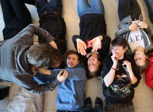 Zu sehen sind einige Jugendliche die lachend auf dem Boden liegen und mit ihren Armen eine Person über sich hinweg transportieren.
