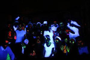 Zu sehen sind Jugendliche, die sich mit Neonfarben bemalt haben und auf einer Schwarzlichtparty tanzen.