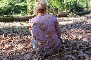 Zu sehen ist eine junge Frau im Wald, die auf dem belaubten Boden sitzt. Ihr Rücken ist voller Laubblätter, die dort hängengeblieben sind.
