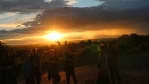 Das Bild zeigt eine kleine Gruppe von Jugendlichen während eines farbintensiven Sonnenuntergangs. Einer der Jungen streckt seine Hand nach oben Richtung untergehender Sonne, sodass es aussieht, als würde er die Sonne in seinen Händen halten.