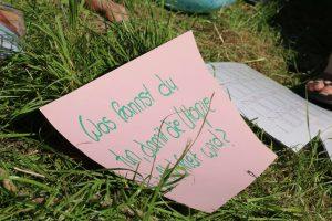 """Ein Zettel liegt auf einer Wiese. Darauf steht """"Was kannst du tun, damit die Utopie Wirklichkeit wird?"""""""