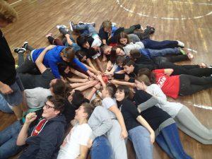 Zu sehen ist eine Gruppe Jugendlicher, die in einem Kreis auf dem Boden liegen. Dabei berühren sie mit jeweils einer Hand einen Ball, der in der Mitte des Kreises liegt.