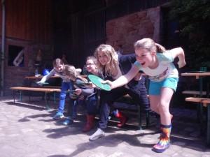 Das Bild zeigt fünf Mädchen mit Plastiktellern in der Hand, die sich scheinbar auf ein Wettrennen vorbereiten.