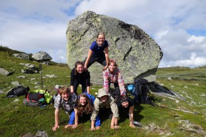 Das Bild zeigt gutgelaunte Jugendliche in der freien Natur beim Bilden einer menschlichen Pyramide vor einem großen Felsen.