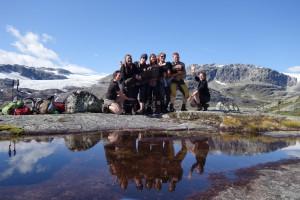 Ein Gruppenfoto junger Menschen beim Wandern. Einer der Männer wird dabei von den anderen Mitgliedern quer getragen. Die Gruppe spiegelt sich in einem davorliegenden Bach. Im Hintergrund ist eine karge Berglandschaft zu erkennen.
