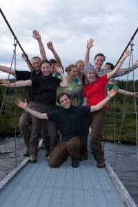 Eine Gruppe junger Menschen, stehen auf einer schmalen Hängebrucken und posieren für ein Gruppenfoto. Dabei strecken sie ihre Hände euphorisch in die Luft.