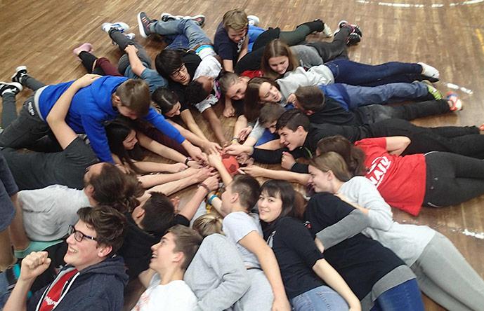 Alle liegen auf dem Boden und greifen nach dem Ball