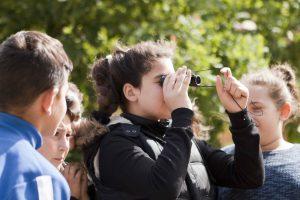 Jugendliche beobachten Vögel mit Ferngläsern