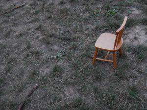 Ein Stuhl auf trockener Wiese. Es ist düster.