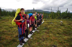 Die Wildnistourgruppe auf einem Steg im Sumpf