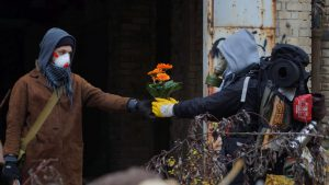 in einem verfallenem Gelände, zwei mit Atemmaske geschütze und vermummte Leute. Das letzte Leben, eine orange blühende Blume, wird an einen Reisesnden, mit großem Rucksack und der relewanten Survival-Ausstattung übergeben.