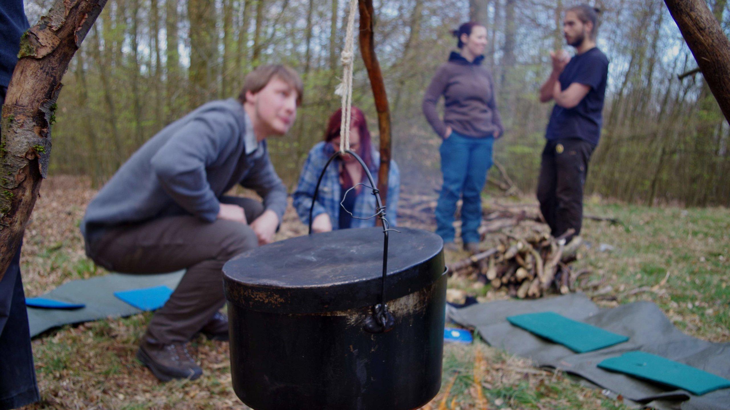 Im Wald, um die Kochstelle herum, Leute verteilt, der Topf im Vordergrund am Dreibein hängend