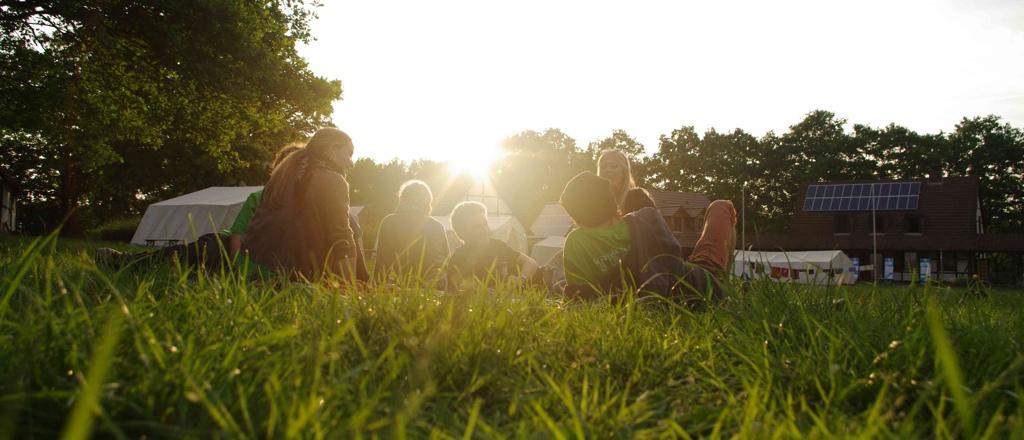 Bild zum Ausnahmezustand: Jugendliche sitzen auf einer Wiese