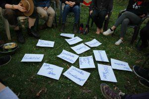 Sitzkreis, es liegen Zettel auf dem Boden zum ThemaGruppenleitung
