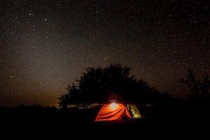 In tiefster Nacht, alle Sterne strahlen am Himmelm, vor dem Schatten eines Baumes, scheint in zwei Zelten noch das Licht.