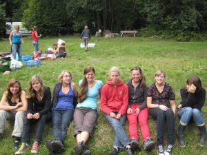 Auf einer Wiese sitzen sieben Freundinnen und drücken sich vor der Arbeit des AUf- bzw. Abbaus.