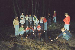 Nachts im Wald, alle stehen um einen Tümpel auf dem Kerzen schwimmen