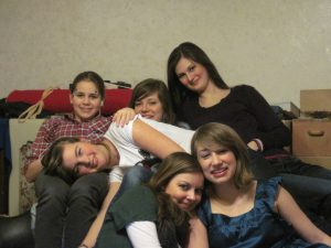 Sechs Freundinnen sitzen als Haufen vor Material