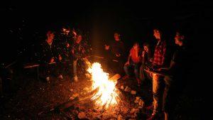 Zu sehen sind Jugendliche, die sich um ein Lagerfeuer versammelt haben.