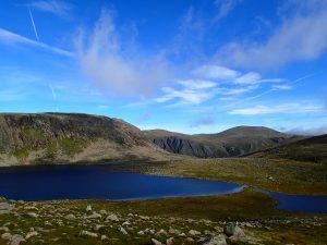 Das Bild zeigt einen tiefblauen See, eingebettet in eine felsige und doch grüne Landschaft.