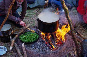 Kochen auf einer Lehmfeuerstelle und Brenneseln dünsten
