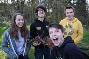 Zu sehen ist eine Gruppe von vier Jugendlichen. Zwei von ihnen schneiden eine Grimasse.
