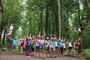 Das Bild zeigt eine große Gruppe von Mädchen, die begeistert die Arme in die Höhe strecken.